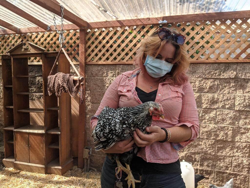 mulher segurando galinha no colo